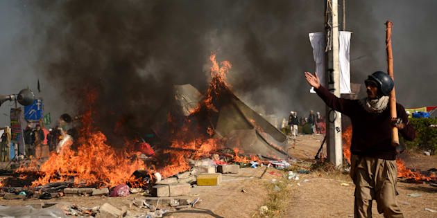 A protester walks near burning tents during clashes with police at Faizabad junction in Islamabad, Pakistan November 25, 2017. REUTERS/Stringer