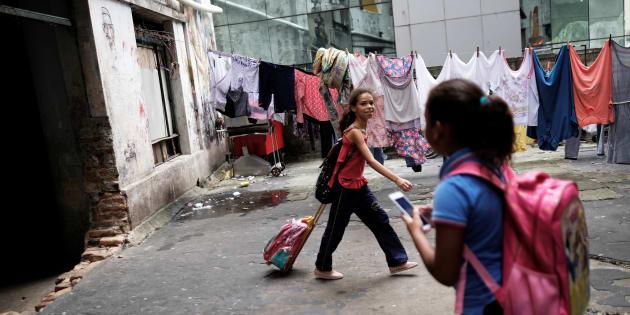 Crianças voltam da aula em fábrica ocupada por sem-teto em São Paulo.