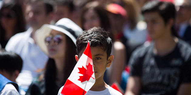A young boy holds a Canadian flag while watching a special Canada Day citizenship ceremony in West Vancouver, B.C., on July 1, 2017.
