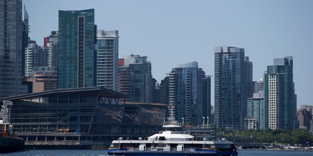 A Seabus commuter vessel with condo towers in the background in Vancouver, B.C., Tuesday, July 11, 2017. The city of Vancouver is considering restricting ownership of housing to local residents.