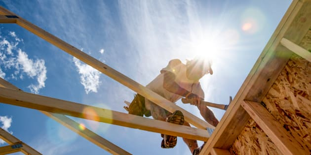 Manual laborer poised on a new construction hammering a piece of frame work with The sun and a partly cloudy blue sky in the background.