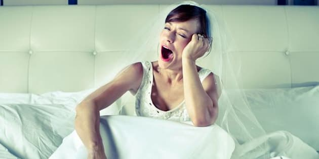 A young woman sitting on a bed wearing a wedding dress and veil yawning.