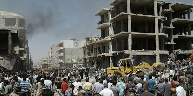 Syrians gather at the site of a bomb attack in Syria's northeastern city of Qamishli.