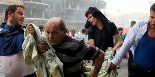 BAGHDAD, IRAQ - JULY 03: (EDITORS NOTE: Image contains graphic content.) Iraqi people carry a wounded citizen after a suicide car bombing, claimed by the terrorist organization DAESH, in the Karrada neighborhood of Baghdad, Iraq on July 03, 2016. It is reported that 60 people were killed and 100 wounded in the blast. (Photo by Amir Saadi/Anadolu Agency/Getty Images)