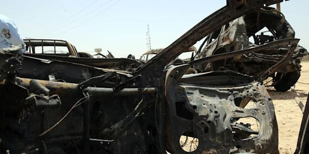 An Iraqi policeman walks past damaged cars as he inspects the site of a suicide bomb attack, claimed by the Islamic State group, at a checkpoint leading to the Husseiniyah area, northeast of the capital Baghdad on July 13, 2016. A suicide bomber detonated an explosives-rigged vehicle killing at least four people and wounding 21 people, the officials said.   / AFP / AHMAD AL-RUBAYE        (Photo credit should read AHMAD AL-RUBAYE/AFP/Getty Images)