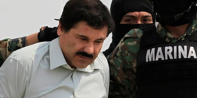 """Joaquin """"El Chapo"""" Guzman (L) is escorted by soldiers during a presentation at the Navy's airstrip in Mexico City February 22, 2014. REUTERS/Henry Romero/File Photo"""