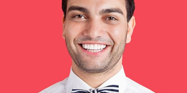 Portrait of a happy mid adult man wearing bow-tie over red background