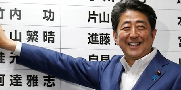 Japan's Prime Minister Shinzo Abe, leader of the ruling Liberal Democratic Party (LDP), puts a rosette on the name of a candidate who is expected to win the upper house election.
