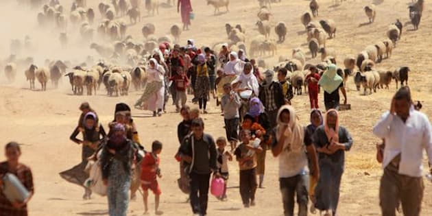 Displaced people from the minority Yazidi sect, fleeing violence from forces loyal to the Islamic State in Sinjar town, walk towards the Syrian border, on the outskirts of Sinjar mountain, near the Syrian border town of Elierbeh of Al-Hasakah Governorate August 10, 2014. REUTERS/Rodi Said/File Photo