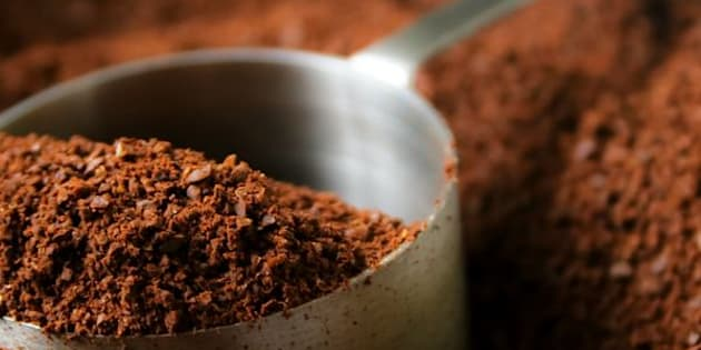 Fresh aroma of coffee grounds in stainless steel scoop.