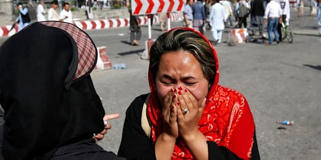 An Afghan woman weeps at the site of a suicide attack in Kabul on Saturday. The attack was claimed by the Islamic State militant group.