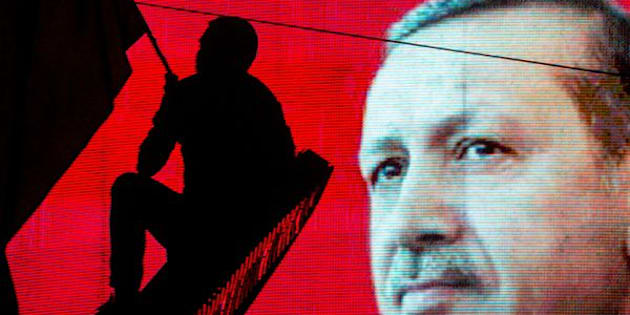 ANKARA, TURKEY - JULY 18: A supporter of Turkish President Recep Tayyip Erdogan waves a flag against an electronic billboard during a rally in Kizilay Square on July 18, 2016 in Ankara, Turkey. Clean up operations are continuing in the aftermath of Friday's failed military coup attempt. Latest figures according to Turkey's Prime Minister Binali Yildirim raises the death toll to 208 with 1491 wounded. Continuing raids across the country have seen 7543 people detained and 316 arrested including high ranking soldiers, judges and police officers.  (Photo by Chris McGrath/Getty Images)