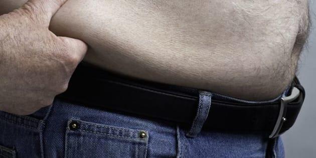Fat man holds fat tummy.