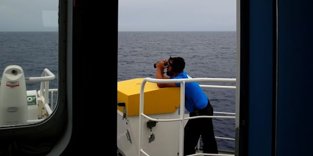 """A crew member on the Migrant Offshore Aid Station (MOAS) ship Topaz Responder looks out for migrants in distress in international waters, off the coast of Libya, June 21, 2016. REUTERS/Darrin Zammit Lupi SEARCH """"RESCUE MOAS"""" FOR THIS STORY. SEARCH """"THE WIDER IMAGE"""" FOR ALL STORIES. MALTA OUT. NO COMMERCIAL OR EDITORIAL SALES IN MALTA"""
