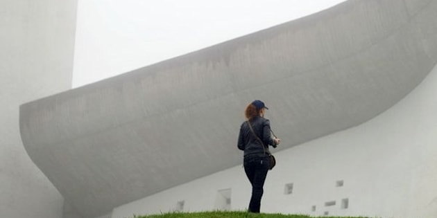 A visitor stands in front of Le Corbusier's Notre Dame du Haut chapel on Sept.9, 2011, in Ronchamp, France. The chapel is one of the architect's most beloved buildings.