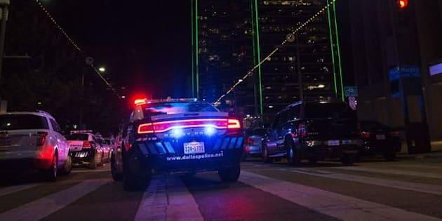 Police cars sit on Main Street in Dallas following the sniper shooting during a protest on July 7, 2016.  A fourth police officer was killed and two suspected snipers were in custody after a protest late Thursday against police brutality in Dallas, authorities said. One suspect had turned himself in and another who was in a shootout with SWAT officers was also in custody, the Dallas Police Department tweeted.  / AFP / Laura Buckman        (Photo credit should read LAURA BUCKMAN/AFP/Getty Images)