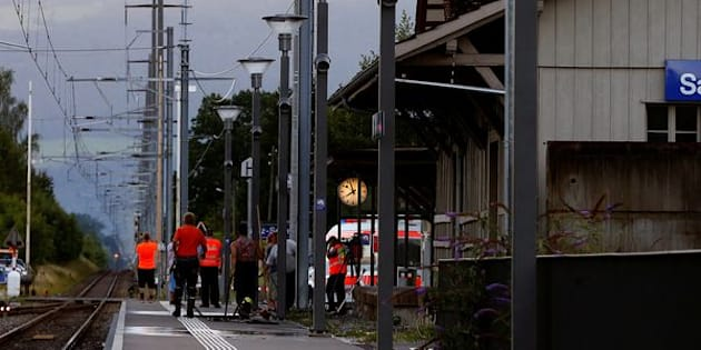 Workers clean a platform after a 27-year-old Swiss man's attack on a Swiss train at the railway station in the town of Salez, Switzerland August 13, 2016.