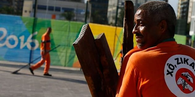 """A workers wears a sign which reads """"Shoo Zika!"""" in Portuguese on his back in the Olympic park."""