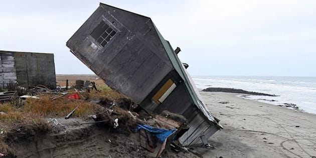 A home destroyed by beach erosion tips over in September 2006 in the Alaskan village of Shishmaref.