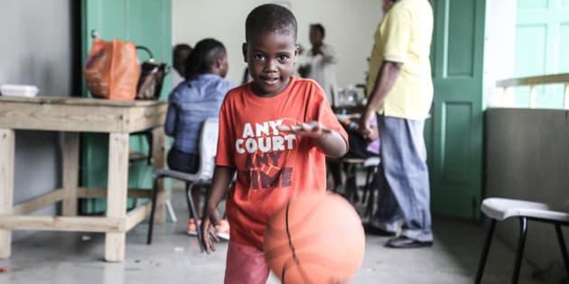 Un jeune garçon joue avec un ballon qu'il vient de recevoir au centre de distribution de l'UNICEF, à Saint John's, à Antigua.