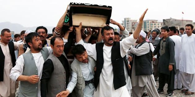 Men carry the coffin of a victim a day after a suicide attack in Kabul, Afghanistan July 24, 2016. REUTERS/Mohammad Ismail