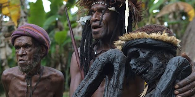 This photo taken on Aug. 7, 2016, shows Eli Mabel of the Dani tribe holding the mummified remains of his ancestor, Agat Mamete Mabel, in the village of Wogi in Wamena, the long-isolated home of the Dani high in the Papuan central highlands.