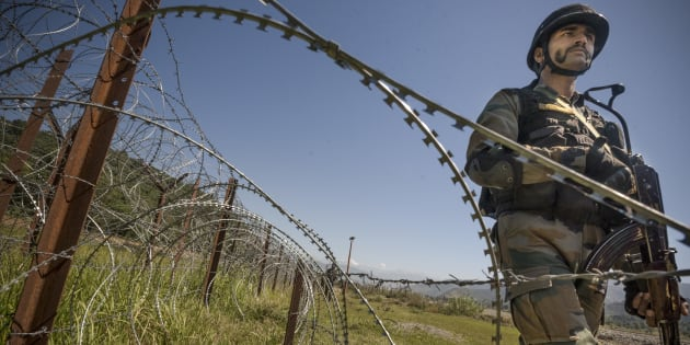 An Indian Army soldier patrols on the fence near the India-Pakistan LOC.