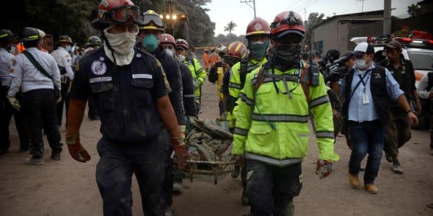Policías y bomberos llevan el cuerpo de una persona en el área afectada por la erupción en la comunidad de San Miguel Los Lotes en Escuintla, Guatemala, este 4 de junio de 2018.