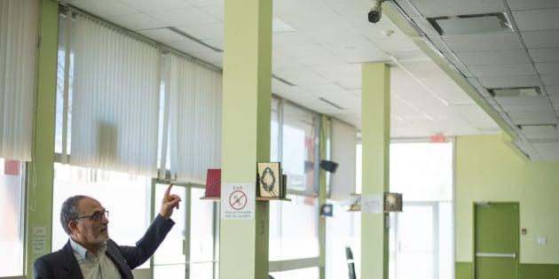 Photo d'archives de Mohamed Labidi, ancien président du Centre culturel islamique de Québec, qui pointe l'une des caméras de surveillance.