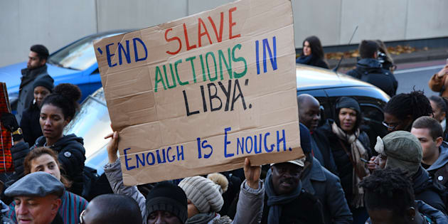 A protester holds a sign-board during an anti-slavery demonstration outside the Embassy of Libya in London, United Kingdom on November 26, 2017 to protest the human rights violations in Libya. (Photo by Alberto Pezzali/NurPhoto via Getty Images)