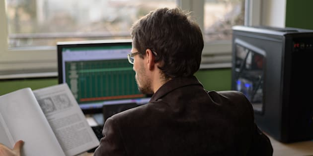young businessman, student trying to solve problem, working on computer - stock photo