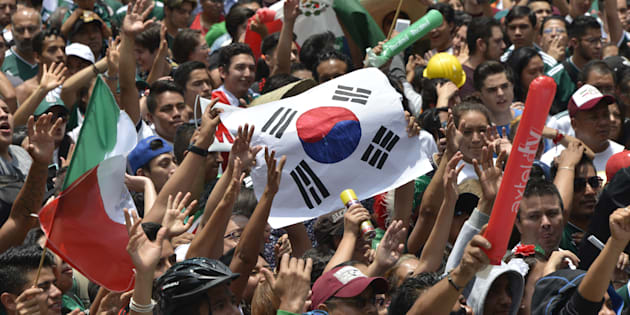 Un fanático del fútbol sostiene una bandera de Corea del Sur mientras miles miran el partido de la Copa Mundial entre México y Suecia en una pantalla en el Monumento al Ángel de la Independencia en la Ciudad de México.