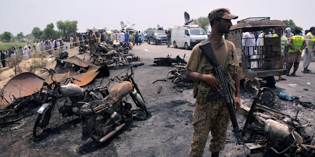 A soldier stands guard amid burnt out cars and motorcycles at the scene of an oil tanker explosion in Bahawalpur, Pakistan June 25, 2017. REUTERS/Stringer