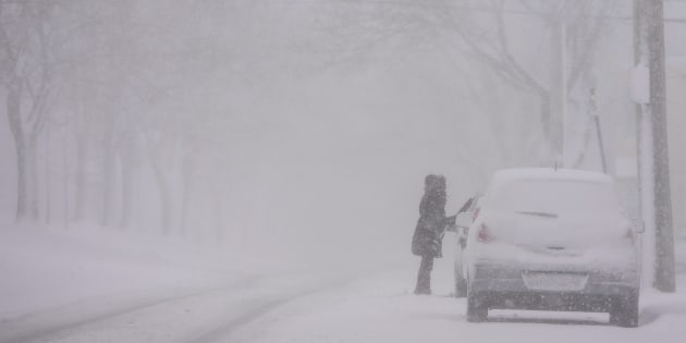 A woman cleans snow off her car as a storm brings white-out conditions to Halifax on Thursday.