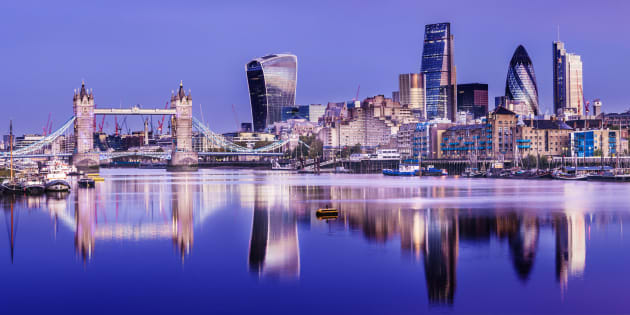 Panoramic view of Tower Bridge and the downtown city skyline at twilight with reflection in the still River Thames, London, England.
