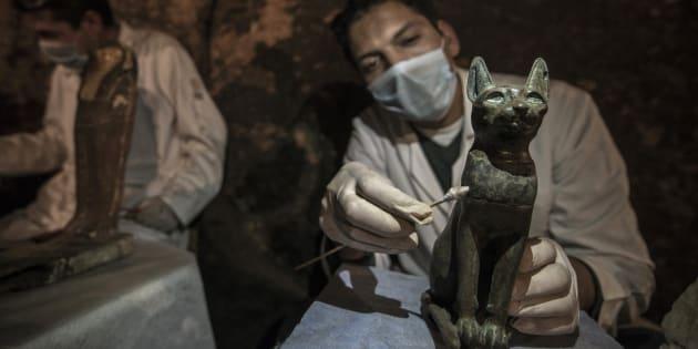 Un archéologue nettoie une statue de chat en bronze datant de l'Égypte ancienne, le 10 novembre à Saqqara.