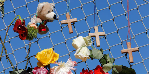 A makeshift memorial featuring crosses, flowers, and a stuffed toy lines a fence near Marjory Stoneman Douglas High School three days after a shooter killed 17 people in Parkland, Fla., on Feb. 17, 2018.