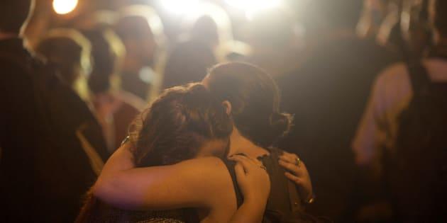 Duas mulheres se abraçam em local próximo à cena do crime, na noite desta quarta-feira (14), no Rio de Janeiro.