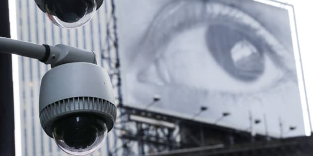 Security cameras are mounted on the side of a building overlooking an intersection in midtown Manhattan. In the background is a billboard of a human eye. (AP Photo/Mark Lennihan)