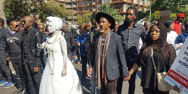 Men leading a march against femicide and gender-based violence
