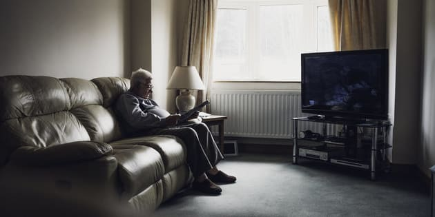 Senior man sitting alone at home. Sitting in his living room with a newspaper and holding a pen in his hands.
