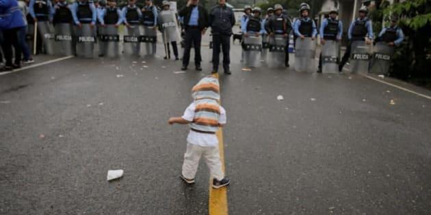 道路を封鎖する警官たちと、移民の子ども