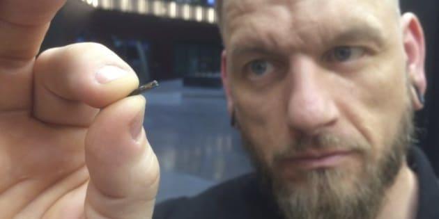 Jowan Osterlund de Biohax Suède tient une micropuce semblable à celles qui seront implantées dans les mains des employés de Three Square Market.