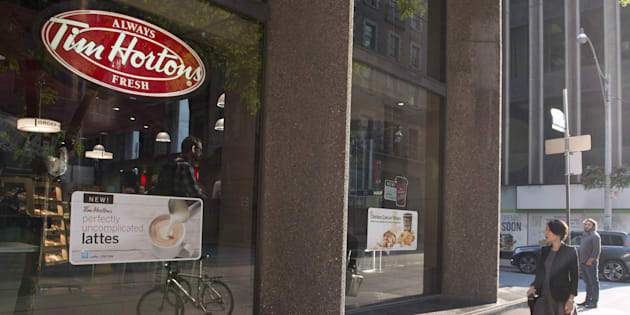 A woman walks pass a Tim Hortons in Toronto on Wednesday Aug. 2, 2017. The parent company of Tim Hortons says restaurants in select markets have increased prices on certain breakfast items.