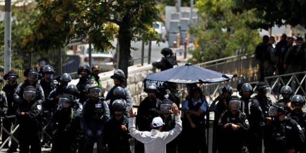 Un hombre palestino cruza ante un grupo de policías israelíes, a las afueras de la Ciudad Vieja de Jerusalén.