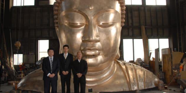山形市で鋳造が進む大仏の顔と八坂住職(右側)ら。大仏の耳だけで2メートルあるという=宝光寺提供