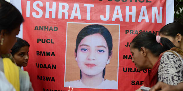 Supporters hold candles in front of a banner bearing the portrait of Ishrat Jahan during a protest in Ahmedabad on July 6, 2013.
