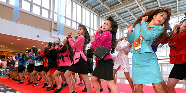 箱形の携帯電話や肩パッド入りの服など、バブル時代をイメージした衣装でダンスする、府立登美丘高校の生徒たち=16日、大阪市港区、遠藤真梨撮影