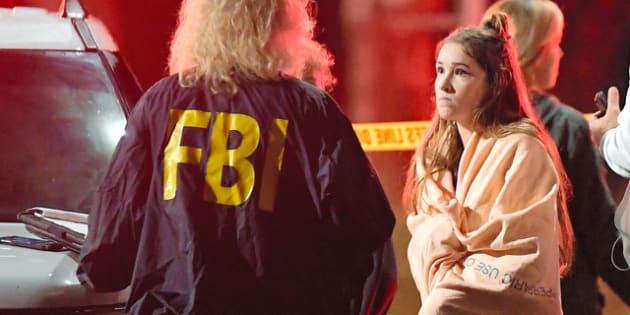 米カリフォルニア州サウザンドオークスの銃乱射事件の現場近くで8日、米連邦捜査局(FBI)関係者に話を聞かれる目撃者とみられる女性=AP