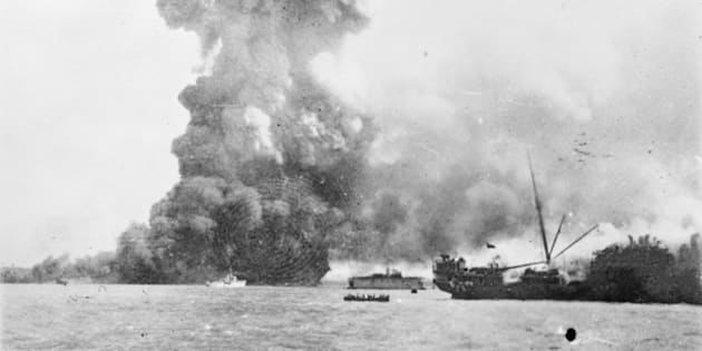 The SS Neptuna explodes at Stokes Hill Wharf, sending a column of debris and smoke hundreds of metres into the air. Directly in front of the explosion is the small Patrol Craft HMAS Vigilant which is undertaking rescue work. In the centre background the floating dry dock holding the Corvette, HMAS Katoomba is visible. In the centre foreground a lifeboat pulls away from the damaged SS Zealandia (right) which was dive bombed and later sunk.